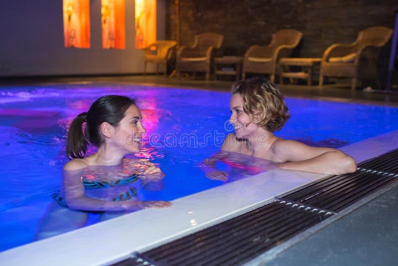 Взрослые имея потеху говоря в бассейне внутри помещения на ноче стоковая фотография rf