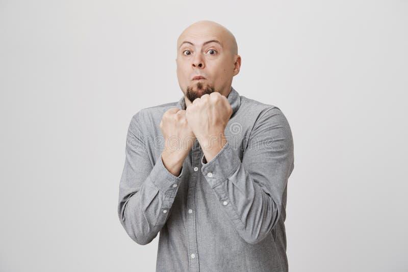 Взрослый бородатый человек с выражением weard готовым для боя держать его кулаки вверх над белой предпосылкой Попытки персоны, ко стоковое изображение