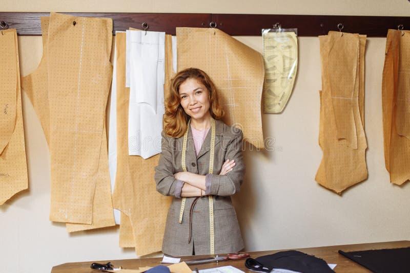 Взрослый модельер работая на atelier, paterns ткани бумаги над предпосылкой стоковое фото