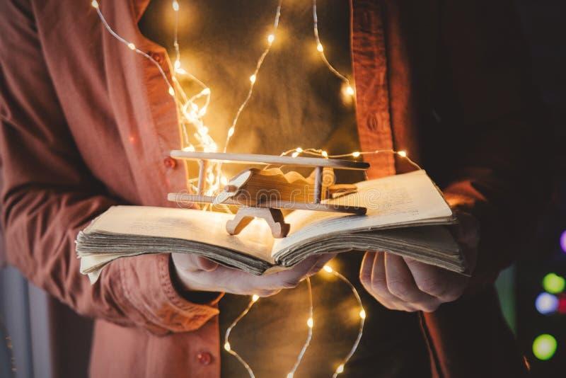 Взрослый молодой кавказский человек держа книгу и игрушку стоковая фотография