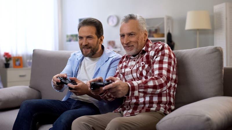 Взрослый отец и сын играя видеоигру имея потеху совместно, досуг стоковые изображения