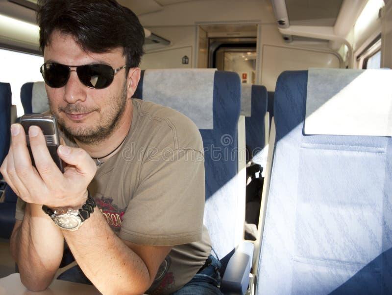 взрослый поезд smartphone используя стоковое фото rf