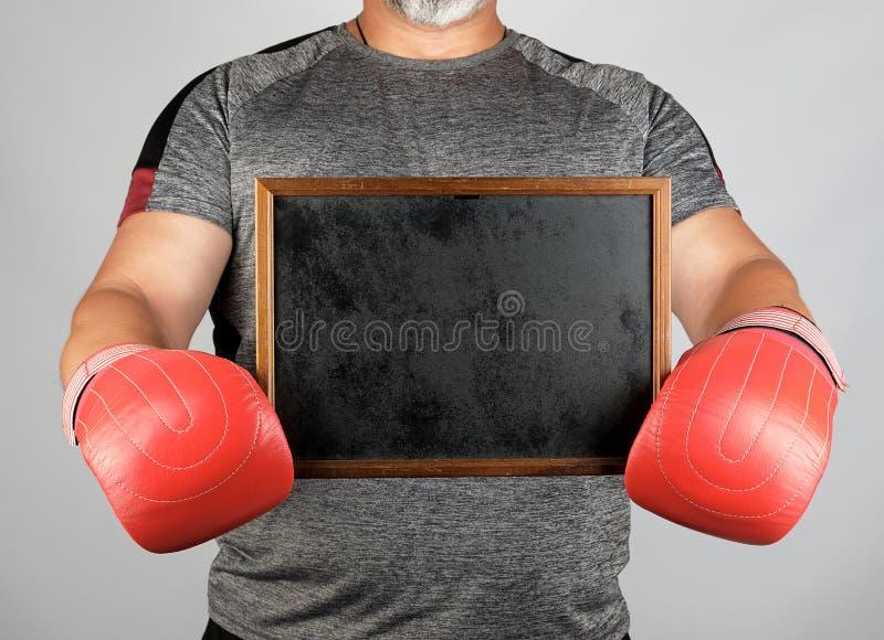 Взрослый спортсмен в серой форме и красных кожаных кладя в коробку перчатках держа пустую черную рамку стоковые фото