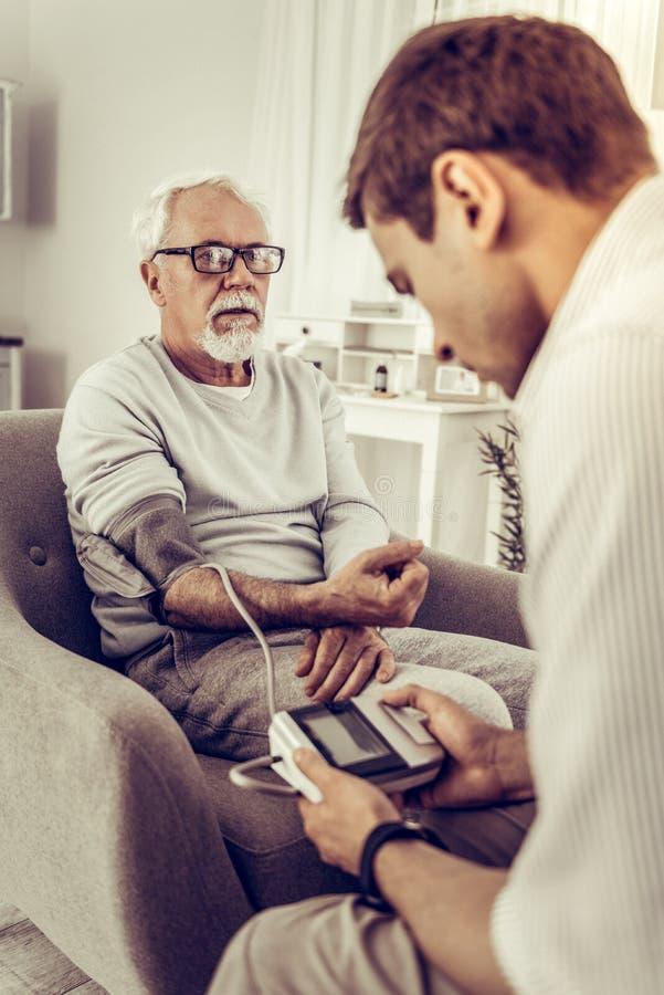 Взрослый сын осторожно принимая кровяное давление его папы стоковые фотографии rf