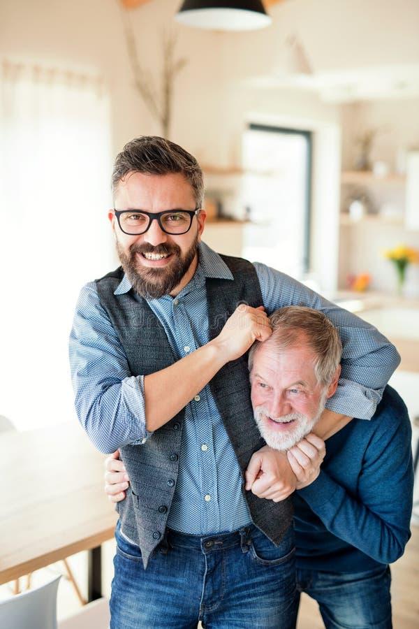 Взрослый сын хипстера и старший отец внутри помещения дома, имеющ потеху стоковое фото