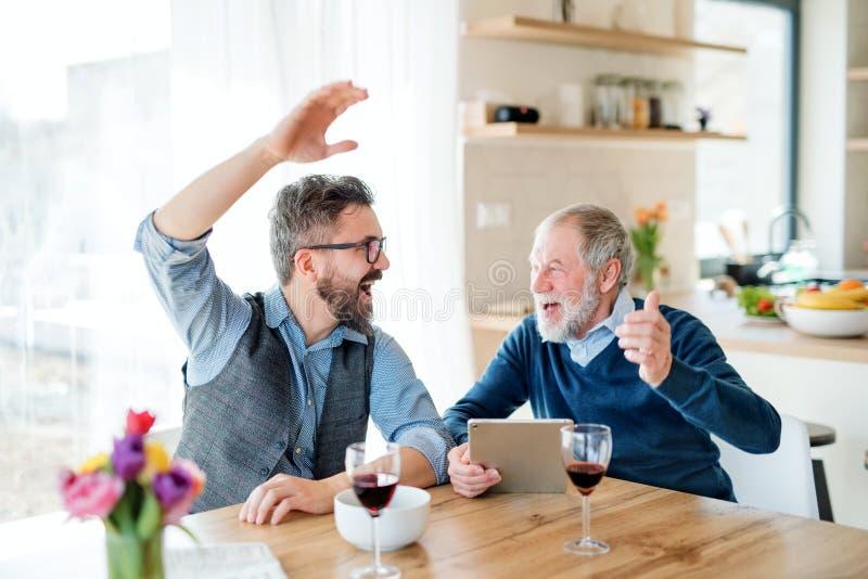 Взрослый сын хипстера и старший отец сидя на таблице внутри помещения дома стоковые фотографии rf
