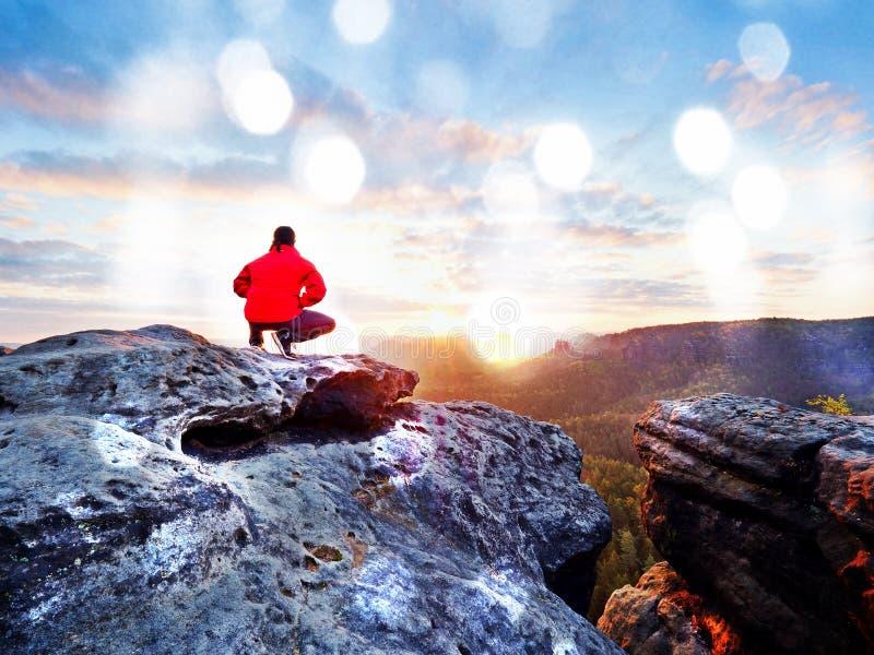 Взрослый турист в черных брюках, красная куртка и темная крышка сидят на крае скалы и смотреть к долине стоковые изображения