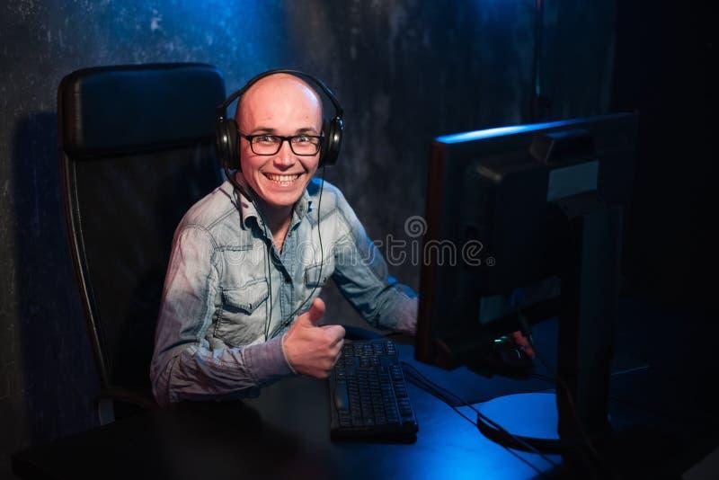 Взрослый gamer сидит дома с компьютером, показывает большие пальцы руки вверх и смотрит в камеру Человек сидя дома на стоковые изображения rf