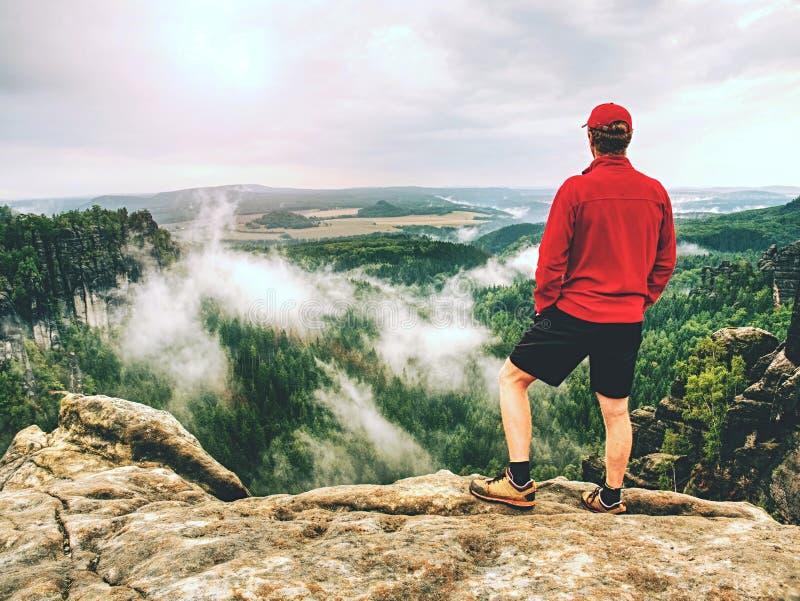 Взрослый hiker в красной рубашке и темных идущих брюках человек высокорослый стоковое изображение