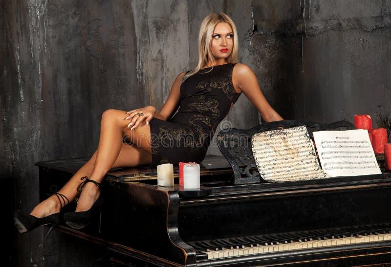 Взрослая белокурая девушка лежа на рояле и смотря прочь стоковое изображение rf