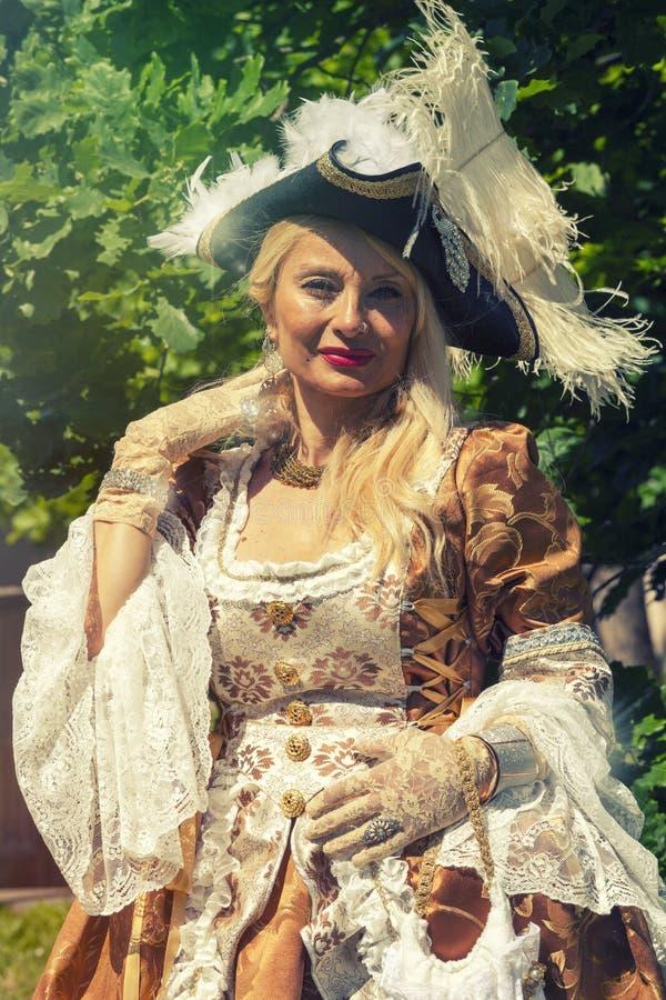 Взрослая белокурая женщина в венецианском костюме напольно стоковое изображение rf