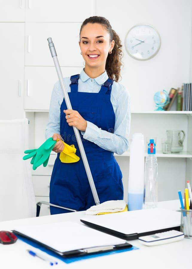 Взрослая женщина в равномерной чистке в офисе стоковое фото rf