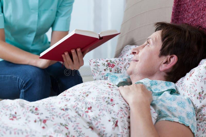 Взрослая женщина лежа в кровати стоковые изображения