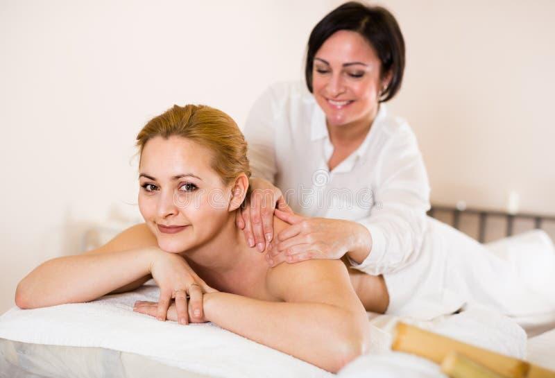 Взрослая женщина на процедуре по массажа в салоне курорта стоковые фотографии rf