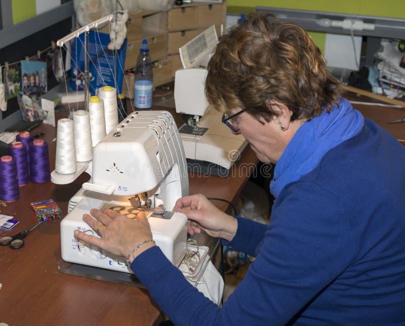 Женщина в мастерской делая одежды стоковые изображения rf