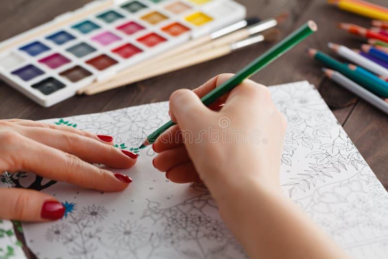 Взрослая женщина сбрасывая стресс путем красить книжка-раскраску для ослабляет стоковая фотография