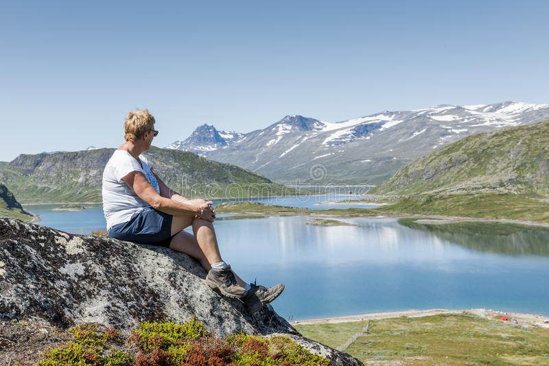 Взрослая женщина сидя на утесе рассматривая открытое море стоковое фото