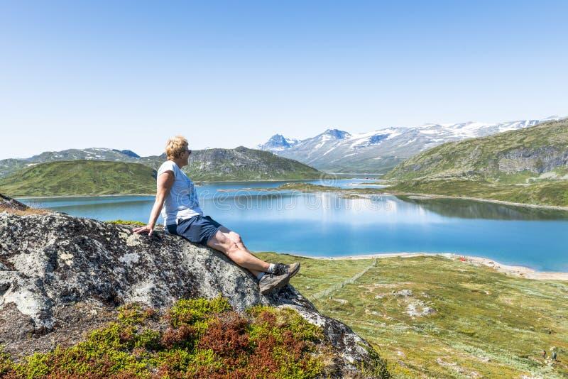 Взрослая женщина счастливая на утесе рассматривая открытое море стоковое фото rf