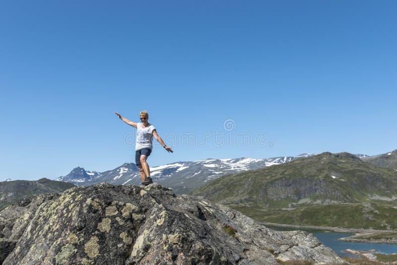 Взрослая женщина счастливая на утесе рассматривая открытое море стоковые изображения rf