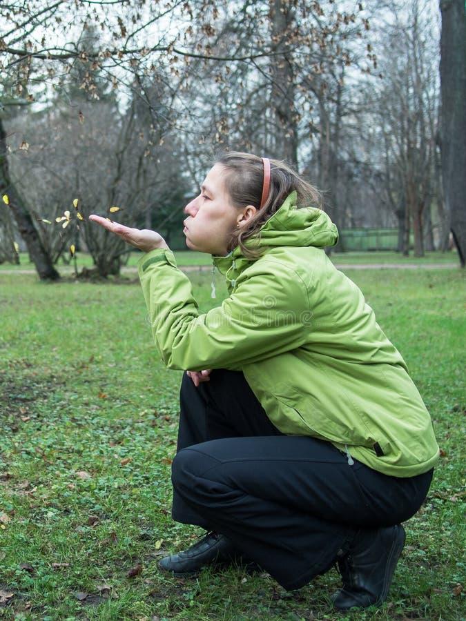 Взрослая женщина дуя на семенах стоковое изображение