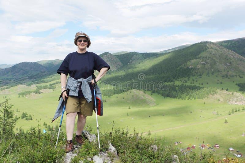 Взрослая счастливая женщина стоя на верхней части горы с ручками стоковые фотографии rf