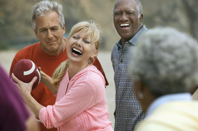 Взрослые друзья играя американский футбол стоковые фотографии rf