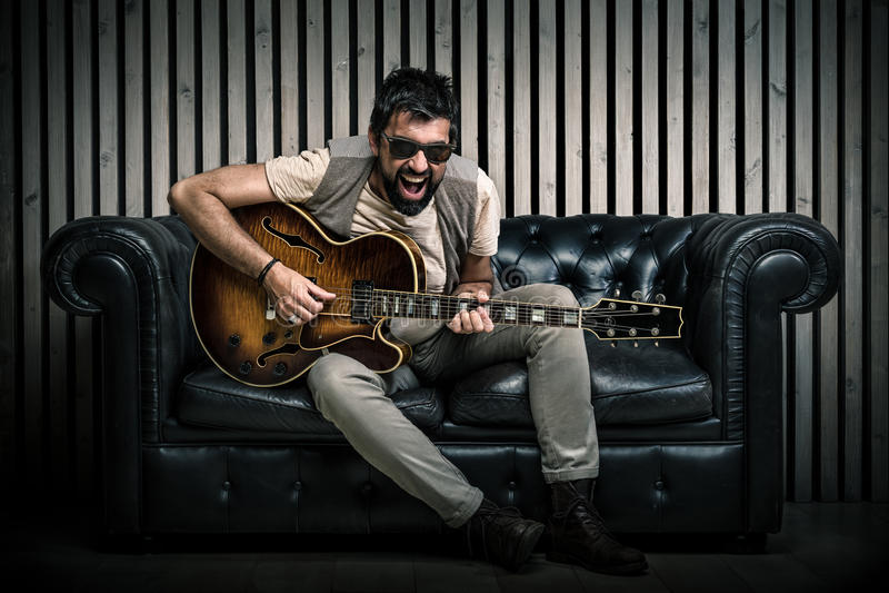 Взрослый кавказский портрет гитариста играя электрическую гитару сидя на винтажной софе Концепция певицы музыки на кресле и стоковые изображения rf