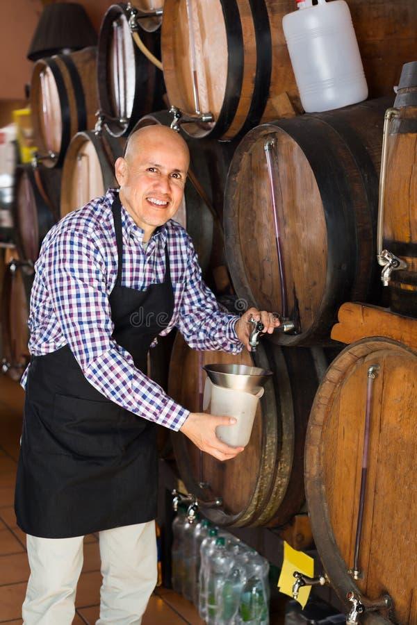 Взрослый создатель вина человека принимая вино от древесины стоковые изображения rf
