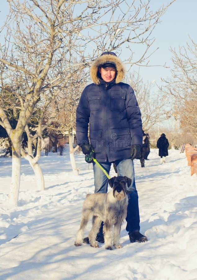 Взрослый человек при его собака стоя на снеге стоковое фото rf
