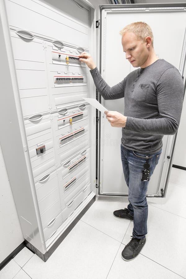 Взрыватель переключателя инженера и читает техническая газета стоковое изображение rf