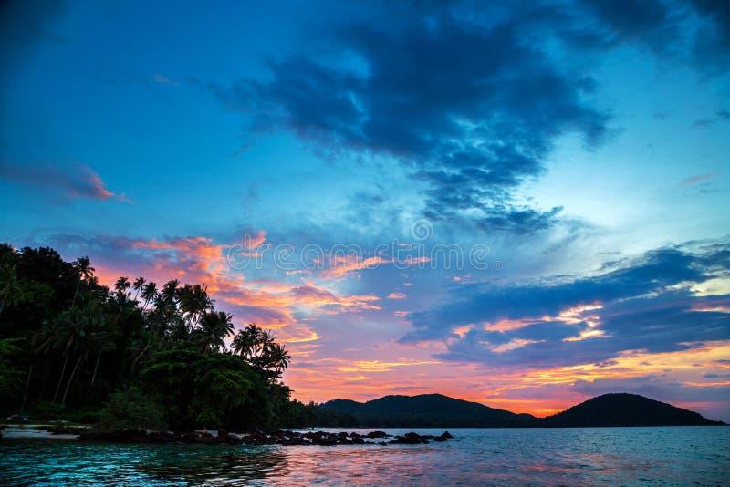 Взрыв облачного неба во время набора солнца с пальмами кокоса силуэта над горной цепью на Mak Таиланде Koh стоковое фото