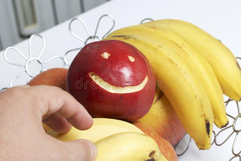 Взятие красное яблоко с высекаенным смайликом в его руке Корзина плодоовощ на заднем плане Несколько яблоки и бананов стоковое изображение rf