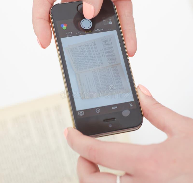 Взятие молодой женщины сняло страницы книги используя smartphone стоковая фотография