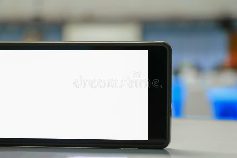 Взятие сотового телефона на белом экране фокуса дела конференц-зала отборного с малой глубиной поля стоковое изображение
