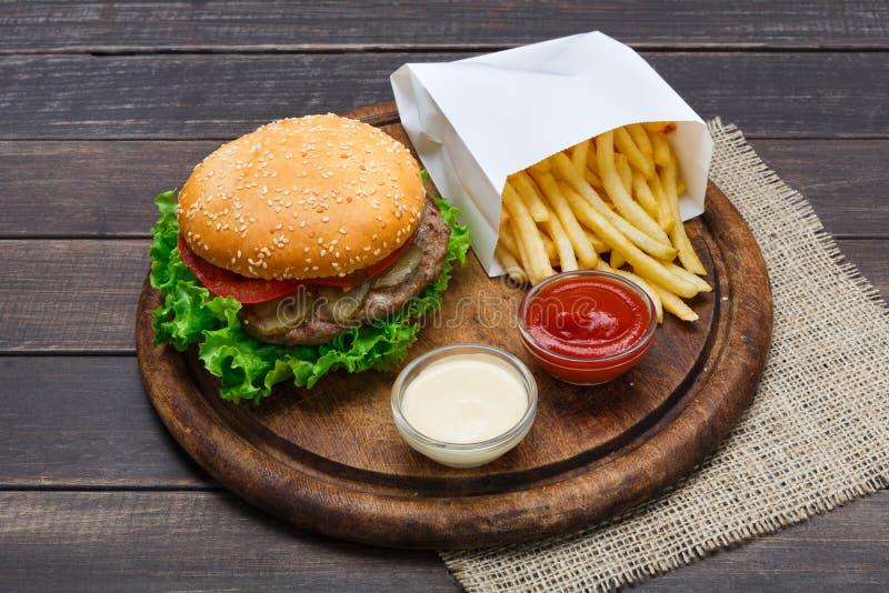 Взятие фаст-фуда отсутствующее Гамбургер и фраи на древесине стоковое изображение