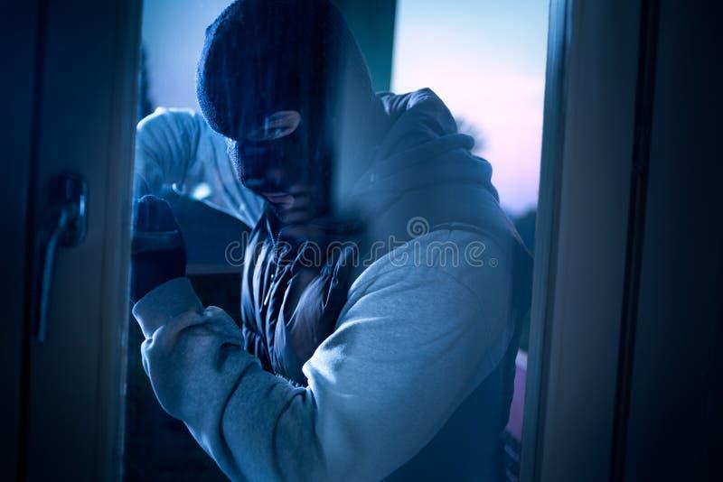 Взломщик при лом ломая в дом стоковые фотографии rf