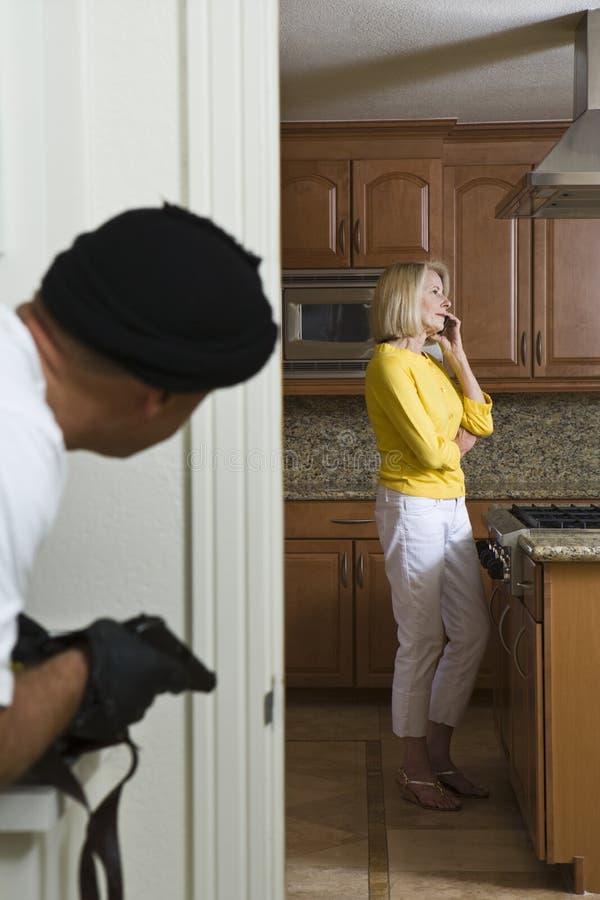 Взломщик при оружие Peeking на женщине стоковые изображения rf