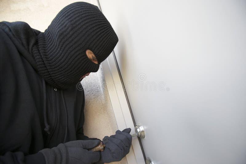 Взломщик работая на замке парадного входа стоковое изображение rf