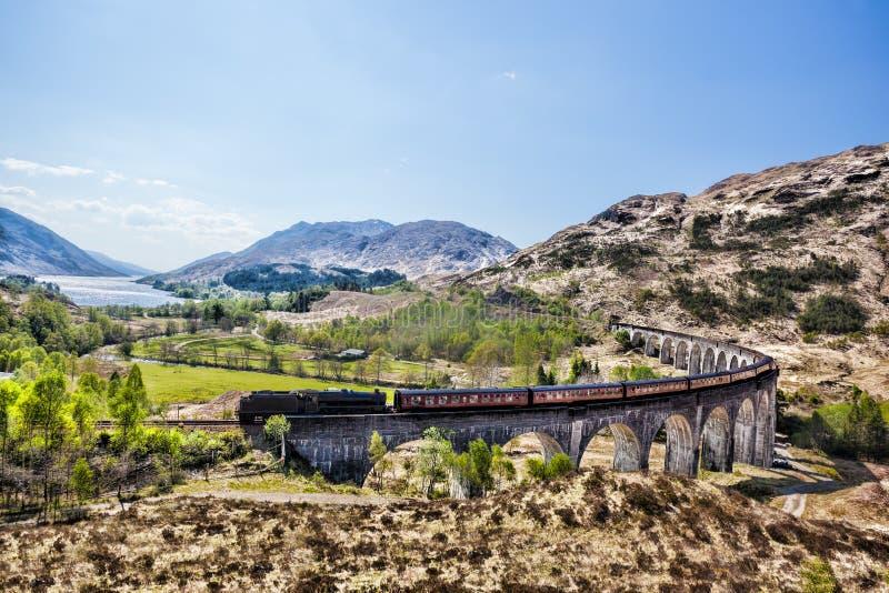 Виадук Glenfinnan железнодорожный в Шотландии с поездом пара Jacobite против захода солнца над озером стоковые изображения rf
