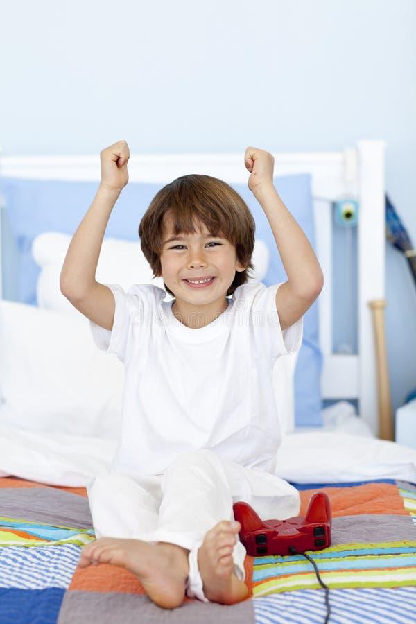 видеоигры мальчика спальни счастливые играя стоковое фото rf