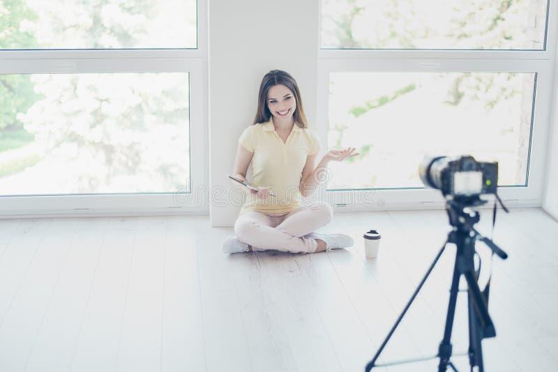 Видеокамера записывает милый блоггер девушки брюнет, говоря стоковое изображение rf