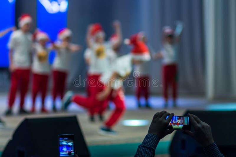 Видео всхода телезрителей на телефоне как дети танцует на этапе Праздничное представление танцоров пролома стоковые фото