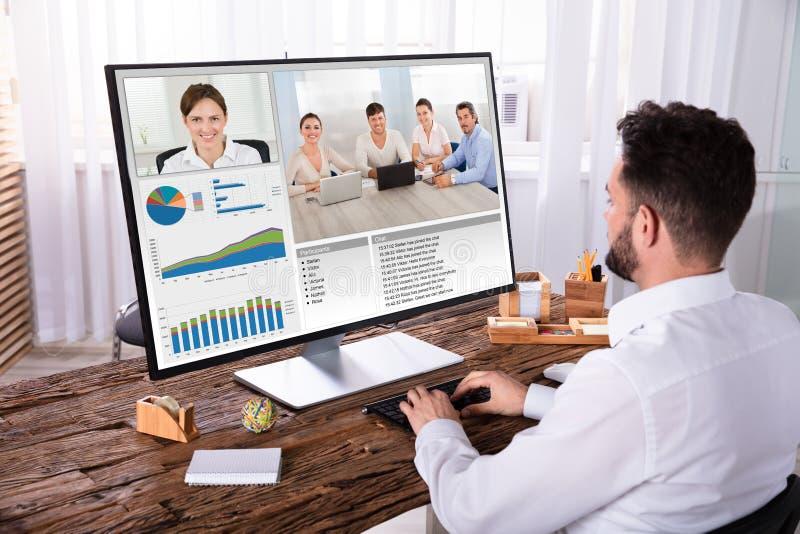 Видео конференц-связь бизнесмена с его коллегами на компьютере стоковое фото