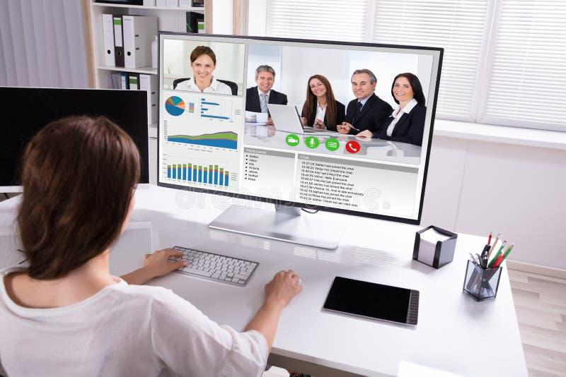 Видео конференц-связь коммерсантки с коллегами на компьютере стоковое фото rf