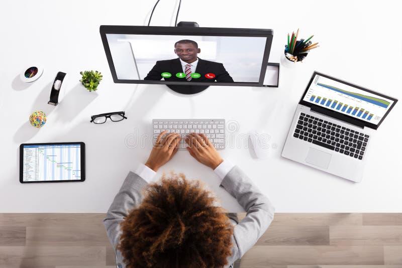 Видео конференц-связь коммерсантки с коллегой на компьютере стоковое фото rf
