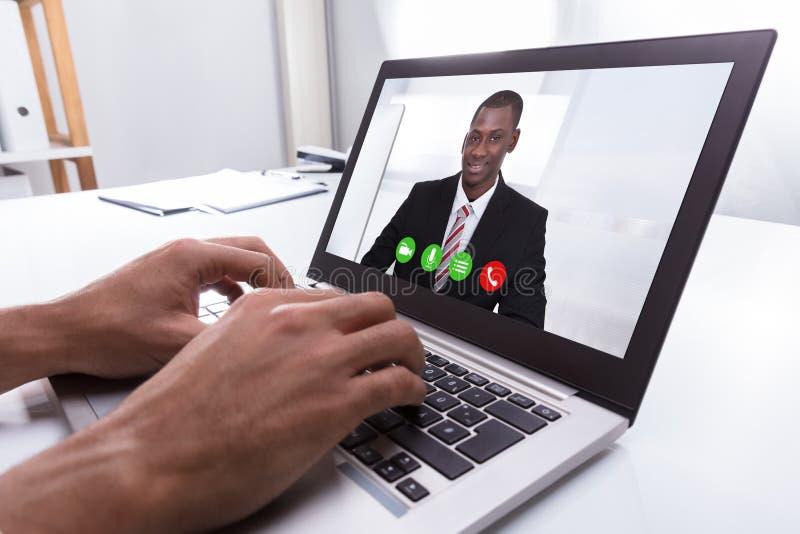 Видео конференц-связь предпринимателя с мужским коллегой на компьтер-книжке стоковое изображение rf