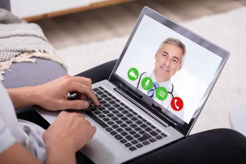 Видео конференц-связь человека с доктором На Ноутбуком стоковые изображения rf