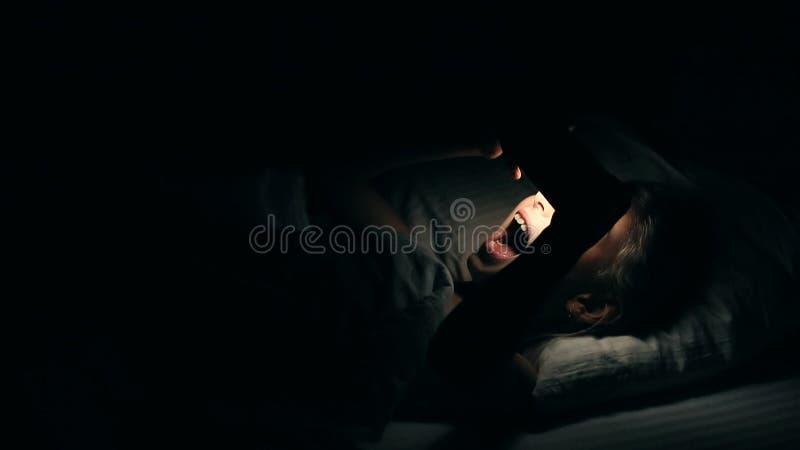 Видео маленькой девочки наблюдая на smartphone лежа вниз в кровати Ноча сняла в спальне при белая девушка используя сотовый телеф стоковое фото rf