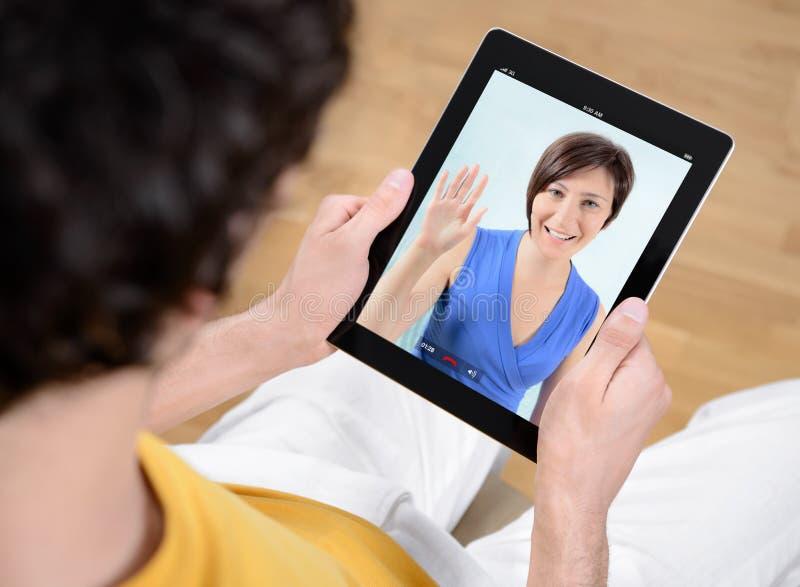 Видео- связь бормотушк через iPad Apple стоковые изображения