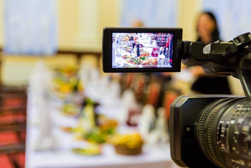 Видео- стрельба на ресторане на банкете Камкордер с дисплеем LCD Люди в зале стоковые фото